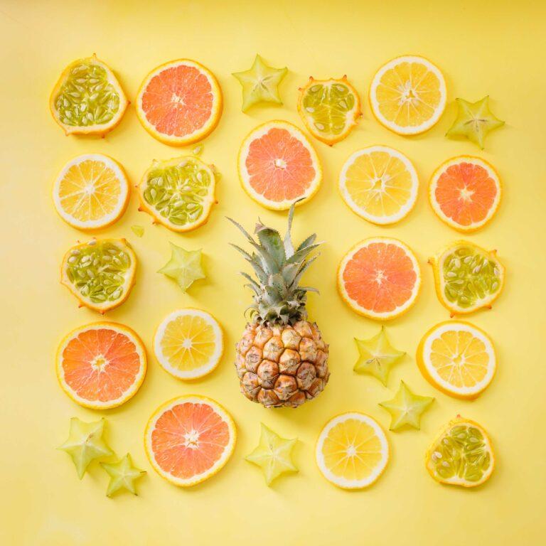 Muchas frutas ricas en vitamina C sobre un fondo amarillo