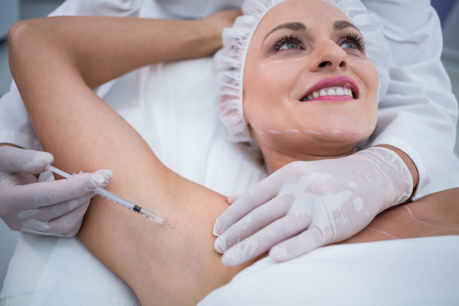 Mujer durante el procedimiento de botox o toxina botulínica en las axilas