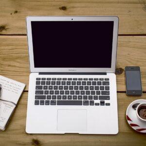Mesa de trabajo de madera con un móvil y un ordenador