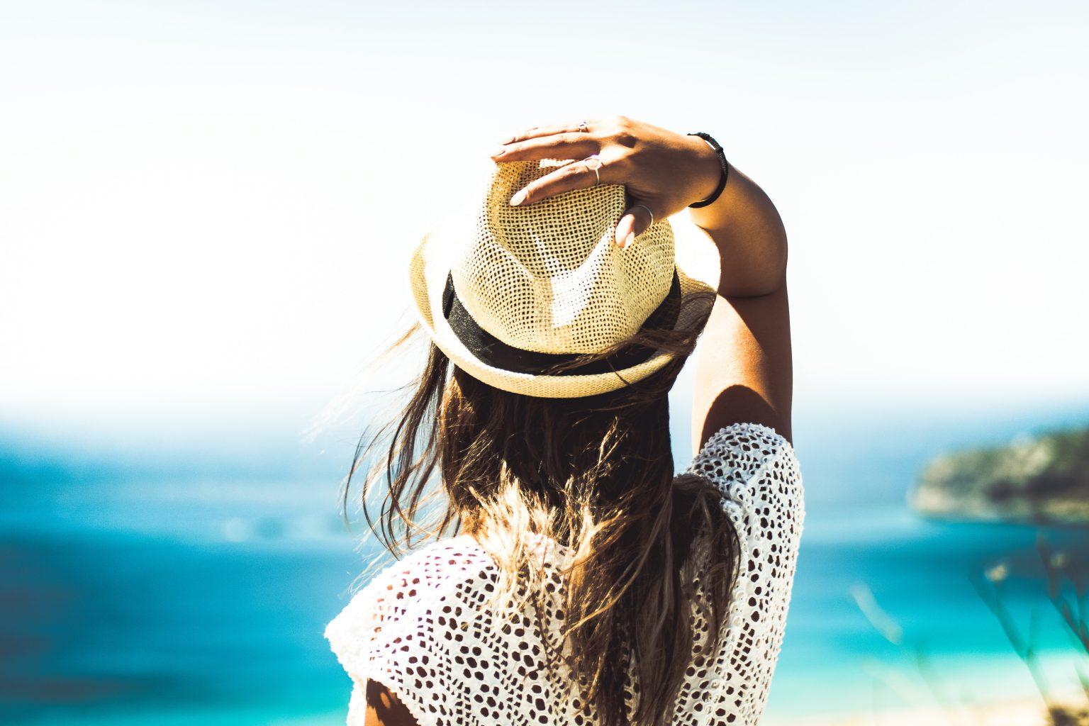 Mujer con gorra en una playa tomando el sol