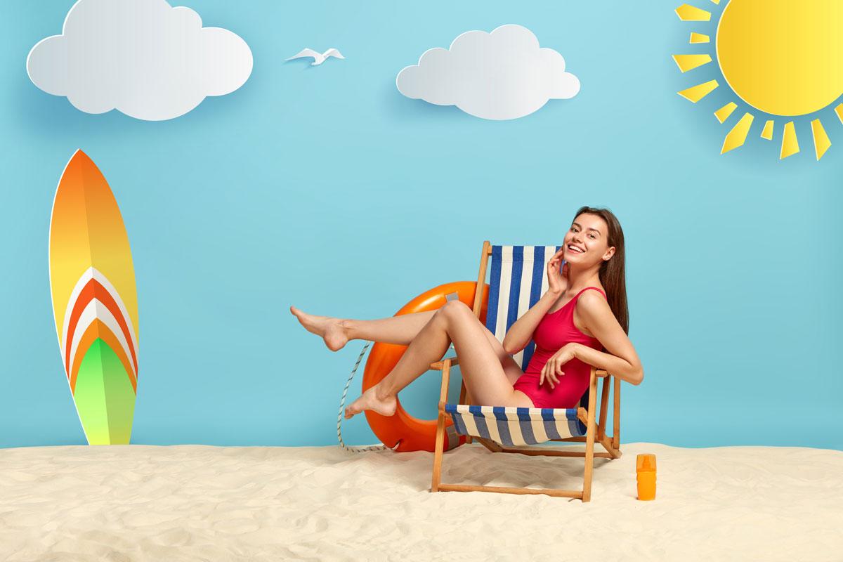 Mujer delgada y guapa con un bikini rojo descansa en un sillón de playa utilizando los mejores protectores solares