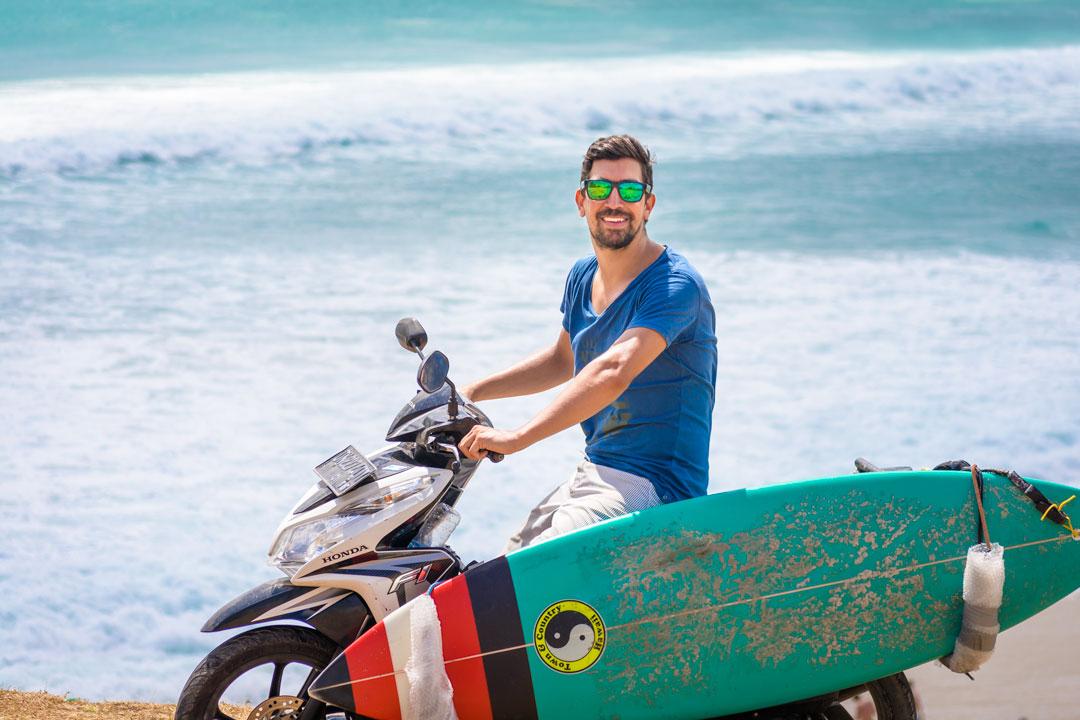 Surfista con la tabla de surf en la moto protegiéndose del sol