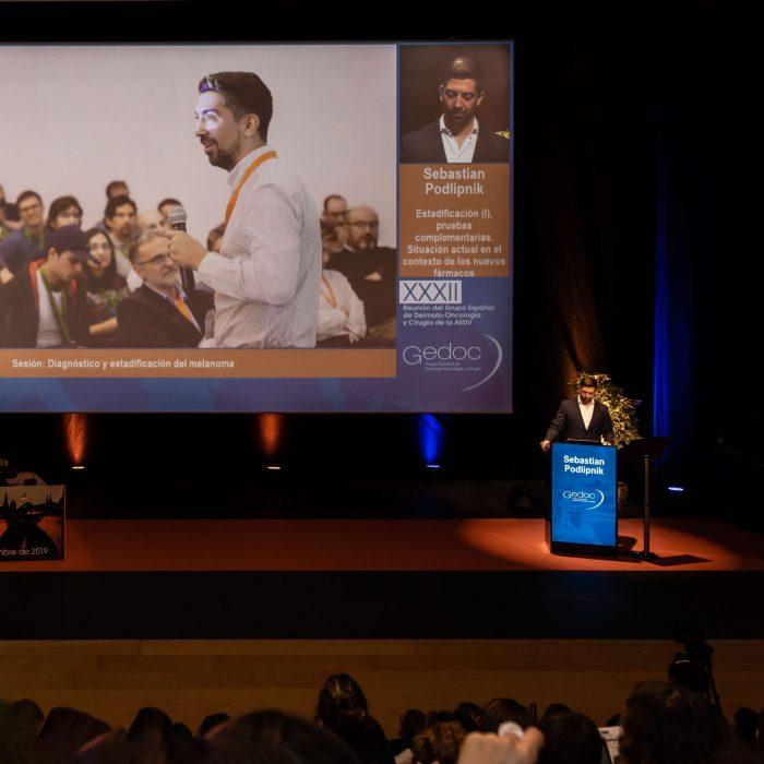 Sebastian Podlipnik presentando durante una conferencia de cáncer de piel en España