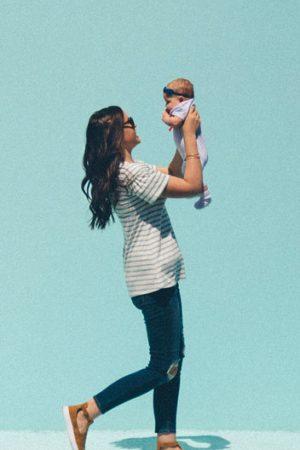 Madre sostiene a su bebe en brazos mientras esta expuesta al sol con protección solar