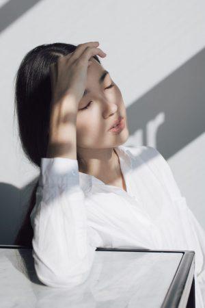 Mujer asiática bajo los rayos del sol utilizando protección solar